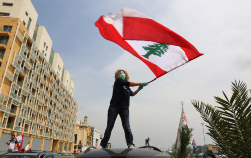 An Anti-government demonstrator holds a Lebanese flag as she stands on top of her car, during a countrywide Coronavirus lockdown in Beirut, Lebanon. (Aziz Taher / REUTERS)